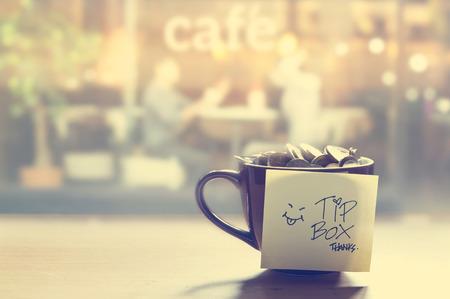 mirror?: caja de propina, moneda en la taza de café en el café delante del espejo, el color de la vendimia y el concepto blando