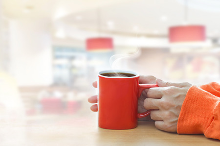 people drinking coffee: Red coffee cup with smoke in woman hand in coffee shop