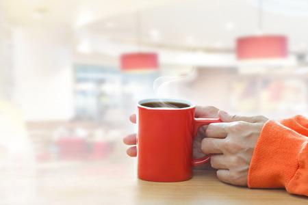 mujer tomando cafe: Taza de café con humo en mano de la mujer en cafetería