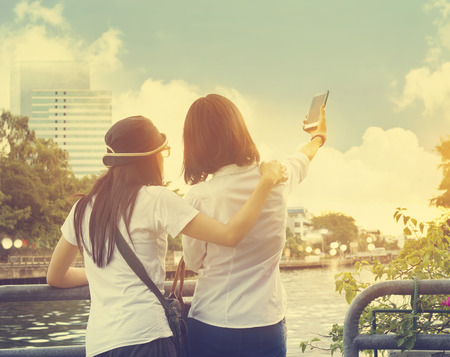 camera girl: Two friends women taking selfie with mobile phone near the river in the nature sky background, Vintage color tone
