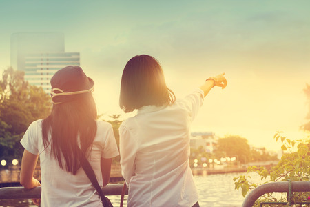 sight seeing: Two women take a sight seeing near the river in the nature sky background, Vintage color tone