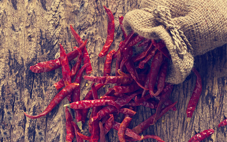 wooden color: Dried red chili peppers in sack with on old wooden background,Vintage color tone Stock Photo