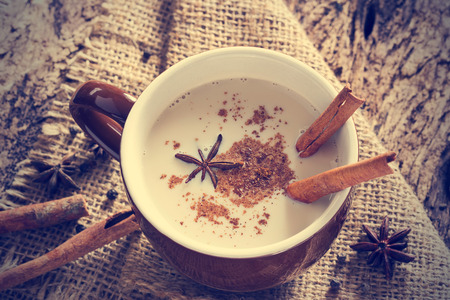 hot drinks: masala chai tea with spices and star Anise, cinnamon stick, peppercorns, on sack and wooden background