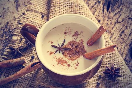 Masala Chai-Tee mit Gewürzen und Sternanis, Zimtstange, Pfefferkörner, am Sack und hölzernen Hintergrund