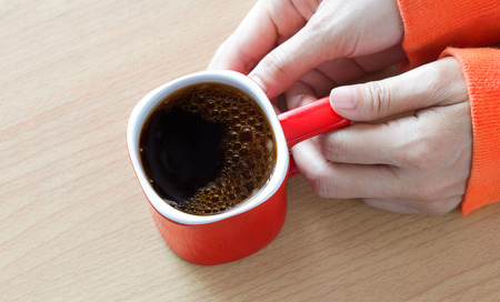 coffee mugs: Red coffee cup with smoke in woman hand on wooden table