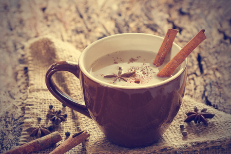 masala chai tea with spices and star Anise, cinnamon stick, peppercorns, on sack and wooden background