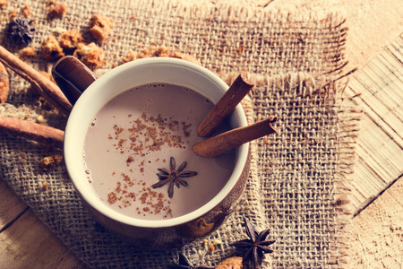 masala chai chocolate with spices and star Anise, cinnamon stick, peppercorns, on sack and wooden background, vintage color tone Stockfoto