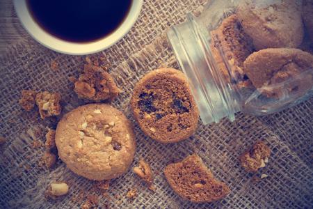 galleta de chocolate: Galletas de chocolate en el tarro de cristal en el saco y café en la mesa de madera