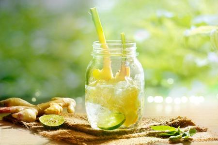 albahaca: jengibre vibrante y colorido con agua de desintoxicación de limón y hierbas de la mañana en el fondo verde de la naturaleza