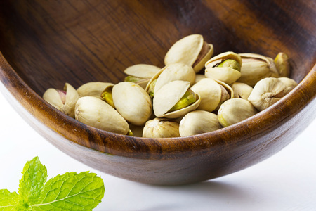 mixed nuts: heap salted pistachio nuts on wooden spoon background