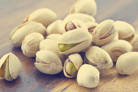 wooden color: heap salted pistachio nuts on wooden background, vintage color tone