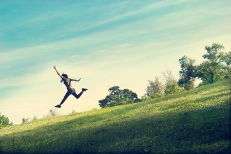 gente feliz: mujer corriendo y saltando divertido relajarse en la hierba verde y flores de campo