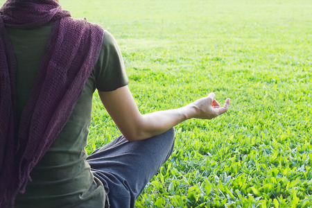 Yoga woman meditating outdoor in park on grass field background, focus on hand