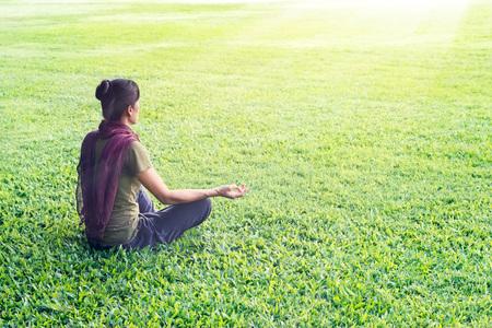 Yoga Frau meditieren im Freien in Park auf Gras Feld Hintergrund Standard-Bild