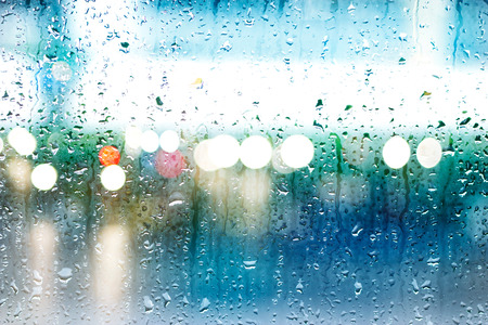 focus on: Abstract drops of rain on colorful glass background, street Lights, soft focus