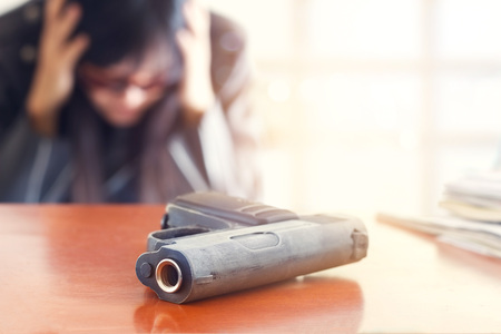 gun man: Business man depressed from failure of business and gun on the table, selective focus on front gun, blank text