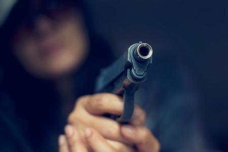 Frau zeigt eine Pistole auf das Ziel auf dunklem Hintergrund, selektiven Fokus auf Front gun