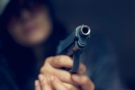 spy girl: Woman pointing a gun at the target on dark background, selective focus on front gun