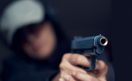 belle brunette: Femme pointant une arme sur la cible sur fond sombre, mise au point s�lective sur le pistolet avant