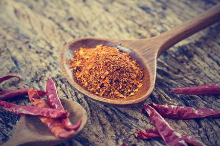chilly: chilly powder with red dried chilies in wooden spoon on old wooden background Stock Photo