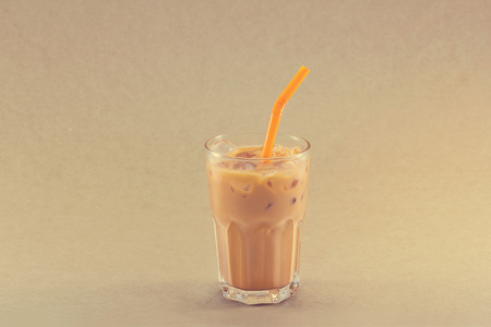 warm color: ice tea with milk in glass cup on grain paper background, warm color tone