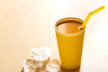 warm color: milk tea in paper cup and ice on wooden background, warm color tone