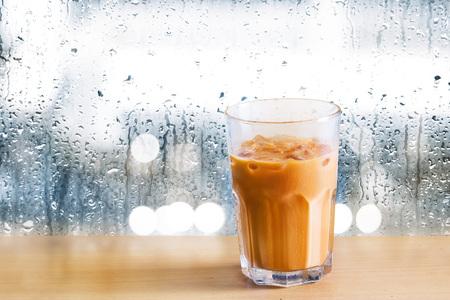 té helado: Té de la leche de hielo en madera y las gotas de lluvia sobre el fondo del espejo