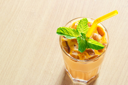 ice tea with milk and mint in glass on wooden background, warm color tone