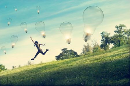 Abstrakte Frau laufen und springen für Glühbirne auf grünem Gras fangen und Blumenfeld