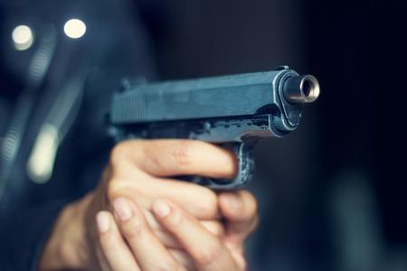 pistola: Mujer apuntando con un arma al blanco sobre fondo oscuro, el enfoque selectivo en arma delante