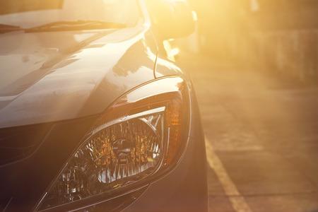 Scheinwerfer des Autos am Licht Sonnenuntergang auf der Straße Hintergrund