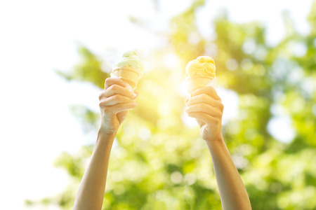 mucky: woman holding melting ice cream waffles cone in hands on summer light nature background