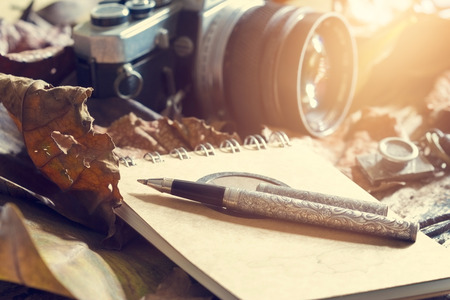 Retro pen on old note pad and camera on dry leaf in jungle background, Vintage color tone