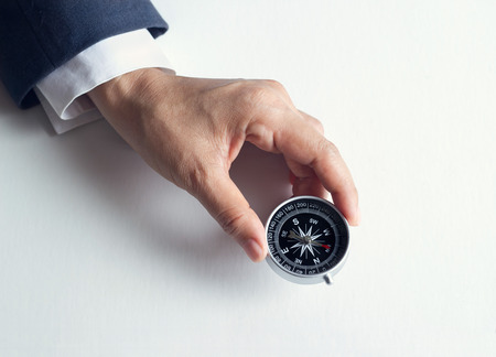 Geschäftsmann mit einem Kompass in der Hand halten auf Papierhintergrund