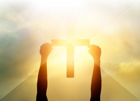 religion catolica: Silueta de la cruz en las manos, símbolo de la religión a la luz y el paisaje a través de una salida del sol, fondo, concepto religioso fe