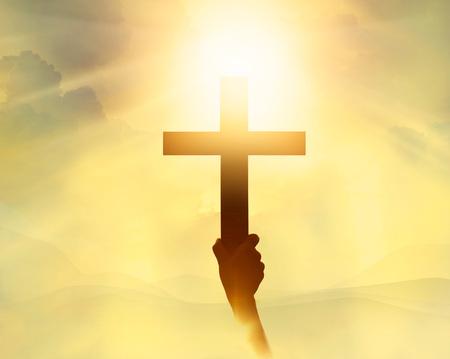 Silhouet van het kruis in de hand, religie symbool in het licht en het landschap op een zonsopgang, achtergrond, godsdienstig, geloof begrip Stockfoto