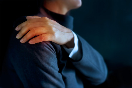 working stiff: heavy shoulder pain of business woman colored in red on dark blue background, Health issues problems