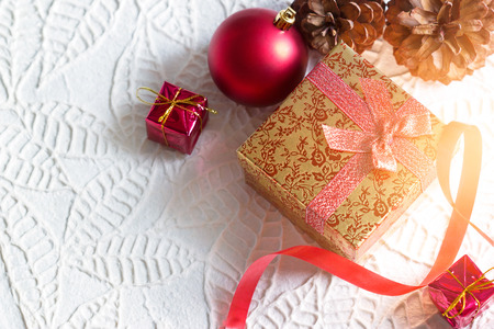 red gift box: Gold christmas gift box tied in ribbon with red bauble on white paper texture background