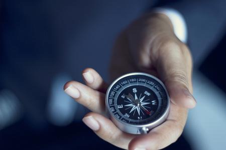 biznes: Biznesmen z gospodarstwa kompasem w ręku, odcień koloru folii wygląd Zdjęcie Seryjne