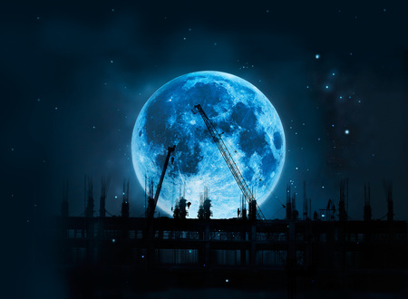 Construction site with cranes and workers full blue moon at night background, Moon original image from NASA.gov Archivio Fotografico