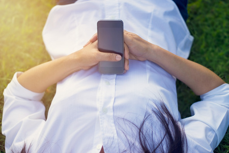 green grass: Woman with mobile smart phone in hand relax on the park