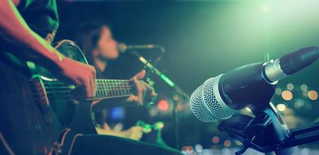 Gitarist op het podium met microfoon voor achtergrond, zacht en blur concept Stockfoto