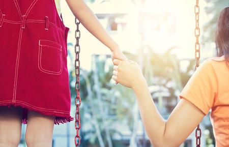 mujeres juntas: La mujer y su hija toman columpio para relajarse. Ella lleva a cabo la mano de su hija para mantener toque cálido. pasaron la escarcha en el jardín de la villa. Foto de archivo