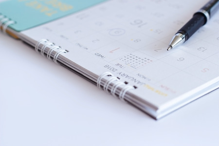 written date: close-up sheet of a calendar and a pen on white background