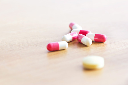 antibiotic pink pill: Pill and capsule on wooden background.