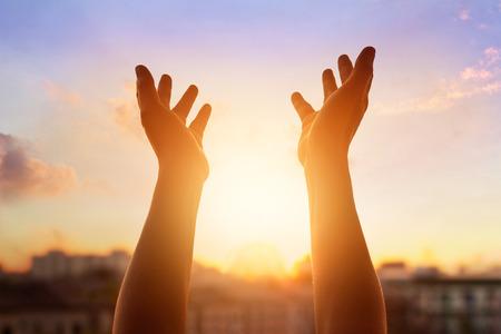 to forgive: Respeto y rezar en la puesta de sol en la ciudad de fondo