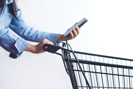 grocery shelves: Closeup of woman with shopping cart and shopping list in smartphone in hand Stock Photo