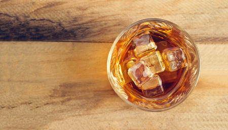 shot: Glass of whiskey with ice on wooden background, Top view and blank text
