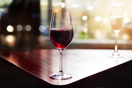 vino: copa de vino en la sala de entretenimiento entre la ventana de fondo la puesta del sol Foto de archivo