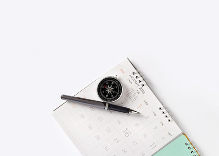 written date: close-up sheet of a calendar with pen and compass on top view, blank text